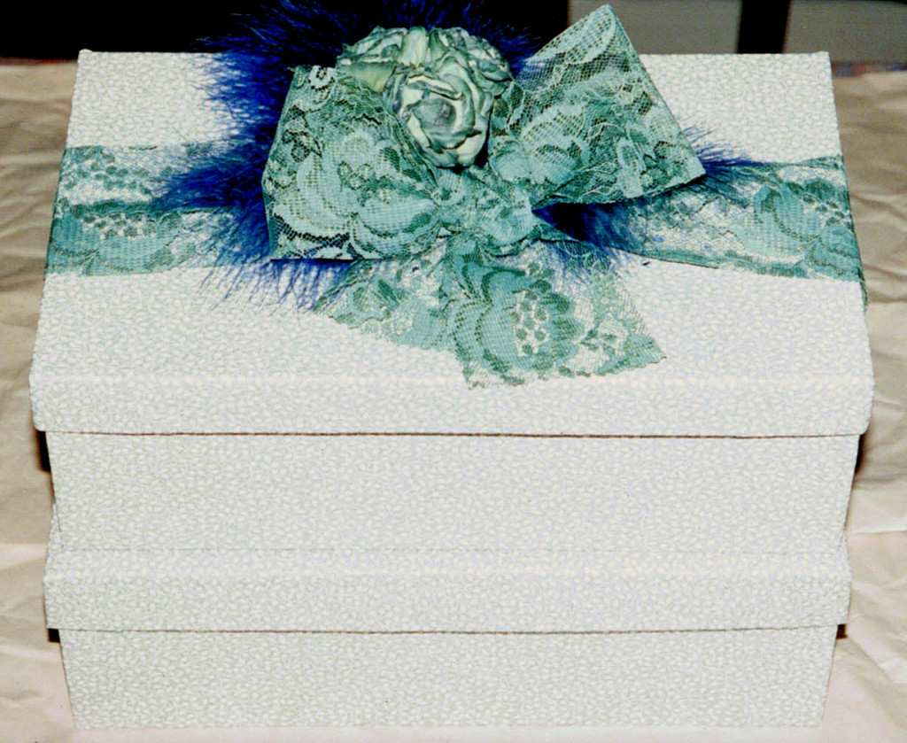 2 shoe boxes wrapped in wallpaper, lace ribbon, wachs roses, deep blue feathers