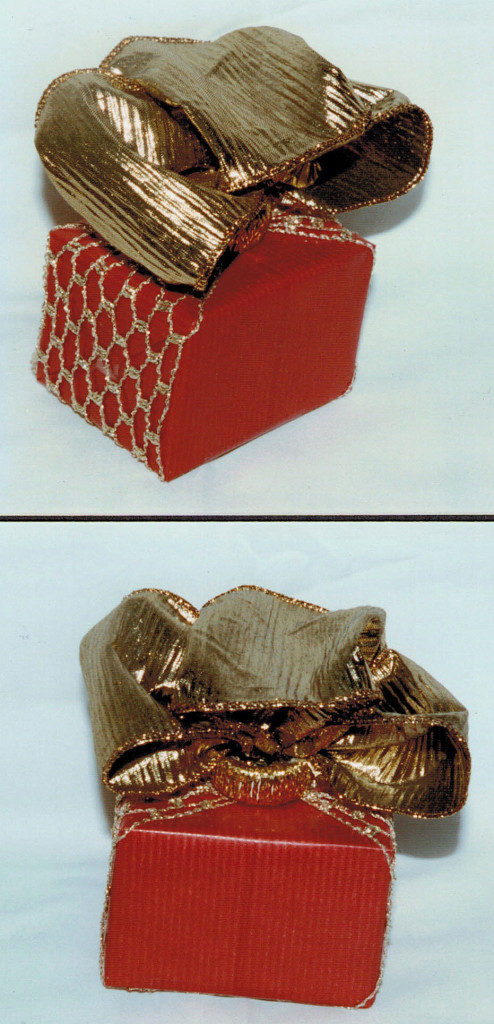small box in gold.net ribbon, large bow hold with a plastic ring